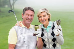 Happy golfing couple with trophy. On a foggy day at the golf course Royalty Free Stock Photos