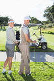 Happy golfing couple turning and smiling at camera Stock Photos
