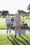 Happy golfing couple walking towards the buggy Royalty Free Stock Photos