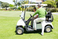 Happy golfing friends setting out on buggy Royalty Free Stock Image