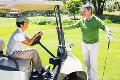 Happy golfing friends setting out for the day on buggy Stock Images