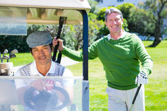 Happy golfing friends setting out smiling at camera on buggy Stock Image