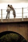 Happy good looking couple leaning on bridge railling kissing Stock Photo