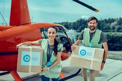 Happy good-looking hard-working volunteers carrying heavy boxes with aid stock image