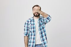Happy good-looking mature male with beard and moustache, smiling and covering his eyes with hand while standing over. Gray background. Father promised not watch Royalty Free Stock Photography