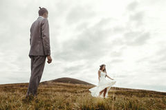 Happy gorgeous bride dancing to groom and having fun, luxury cer. Emony at mountains with amazing view, space for text, boho wedding couple Royalty Free Stock Images
