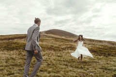 Happy gorgeous bride dancing to groom and having fun, luxury cer. Emony at mountains with amazing view, space for text, boho wedding couple Royalty Free Stock Photography