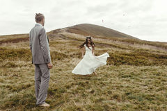 Happy gorgeous bride dancing to groom and having fun, luxury cer. Emony at mountains with amazing view, space for text, boho wedding couple Royalty Free Stock Photo