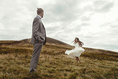 Happy gorgeous bride dancing to groom and having fun, luxury cer. Emony at mountains with amazing view, space for text, boho wedding couple Stock Photos