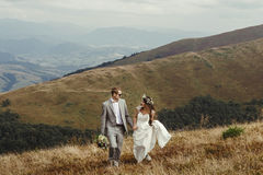 Happy gorgeous bride and groom walking  in sun light holding han Stock Images