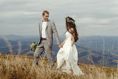 Happy gorgeous bride and groom walking  in sun light holding han Stock Photo