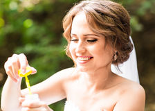 Happy gorgeous  bride have fun with bubble blower outdoors in park Stock Image
