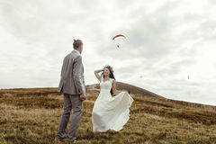 Happy gorgeous bride running to groom and having fun, luxury cer. Emony at mountains with amazing view, space for text, boho wedding couple Stock Photos