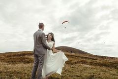 Happy gorgeous bride running to groom and having fun, luxury cer. Emony at mountains with amazing view, space for text, boho wedding couple Royalty Free Stock Image