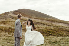 Happy gorgeous bride running to groom and having fun, luxury cer. Emony at mountains with amazing view, space for text, boho wedding couple Stock Photography