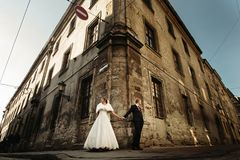 Happy gorgeous bride and stylish groom holding hands and looking. At different sides on background of old building Stock Image