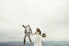 Happy gorgeous bride and stylish groom jumping and having fun, b Stock Photos