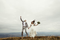 Happy gorgeous bride and stylish groom jumping and having fun, b Stock Image