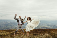 Happy gorgeous bride and stylish groom jumping and having fun, b. Oho wedding couple, luxury ceremony at mountains with amazing view, space for text Stock Photography