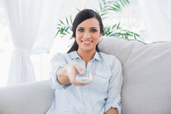 Happy gorgeous brunette changing tv channels Stock Photography