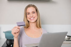 Happy gorgeous model holding laptop and credit card Royalty Free Stock Image