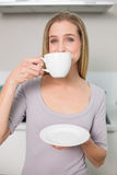Happy gorgeous model holding plate with cup Royalty Free Stock Photos