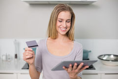 Happy gorgeous model holding tablet and credit card Stock Images