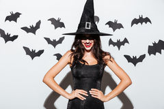 Happy gothic woman in witch halloween costume standing and smiling stock images