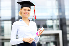 Happy graduate standing outside modern building Royalty Free Stock Photos