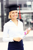 Happy graduate standing outside modern building Royalty Free Stock Images