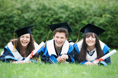 Happy graduate students. Group of three graduation students lying in the park cheerful and happy Royalty Free Stock Image