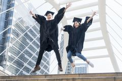 Happy graduate teen people jumping with the graduation gowns in. The happy graduate teen people jumping with the graduation gowns in congratulation ceremony Royalty Free Stock Photos
