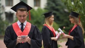 Happy graduate uploading photos from ceremony to social network, memorable event. Stock footage stock video footage