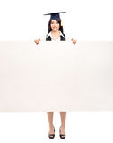 Happy graduate woman holding a blank white banner. Young, beautiful and happy graduate girl with a blank banner isolated on white Royalty Free Stock Photos