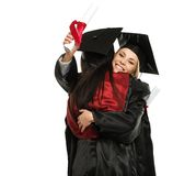 Happy graduated girls. Happy graduated young girls hugging stock images