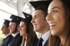 Happy graduates in mortars and gowns, head and shoulders royalty free stock photo