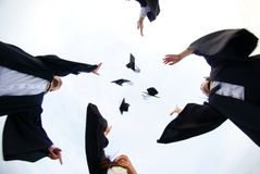 Happy graduates throwing hats. In the air from a low angle directly below them Royalty Free Stock Photo