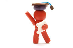 HAPPY GRADUATION. Plasticine figure celebrating graduation with certificate and student hat Stock Photography