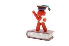 HAPPY GRADUATION. Plasticine figure celebrating graduation with certificate and student hat staying on book Royalty Free Stock Photography