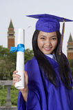 Happy graduation day. Young woman with graduation cap and gown holding her diploma Royalty Free Stock Photo