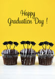 Happy Graduation Day party chocolate cupcakes. With graduation cap hat topper decorations, in yellow, black and white party theme Stock Photography