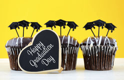 Happy Graduation Day party chocolate cupcakes. With graduation cap hat topper decorations, in yellow, black and white party theme Stock Images