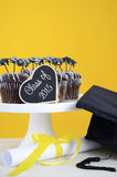 Happy Graduation Day party chocolate cupcakes. With graduation cap hat topper decorations, in yellow, black and white party theme Stock Image