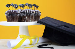 Happy Graduation Day party chocolate cupcakes. With graduation cap hat topper decorations, in yellow, black and white party theme Royalty Free Stock Photos