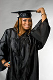 Happy Graduation Girl. A hispanic girl at graduation posing in her cap and gown isolated over a silver background Stock Photo