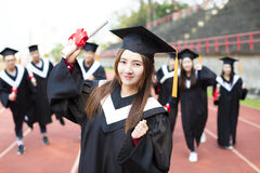 Happy graduation students with diplomas outdoors stock images