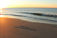 Happy Graduation. Written in sand on the beach during sunrise Stock Photo