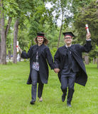 Happy Graduation. Young happy couple running in a green park in the graduation day Royalty Free Stock Image