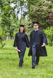 Happy Graduation. Young happy couple walking hand in hand in a green park in the graduation day Stock Photo