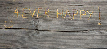 Happy Graffiti carved into wood. Forever Happy Stock Photography